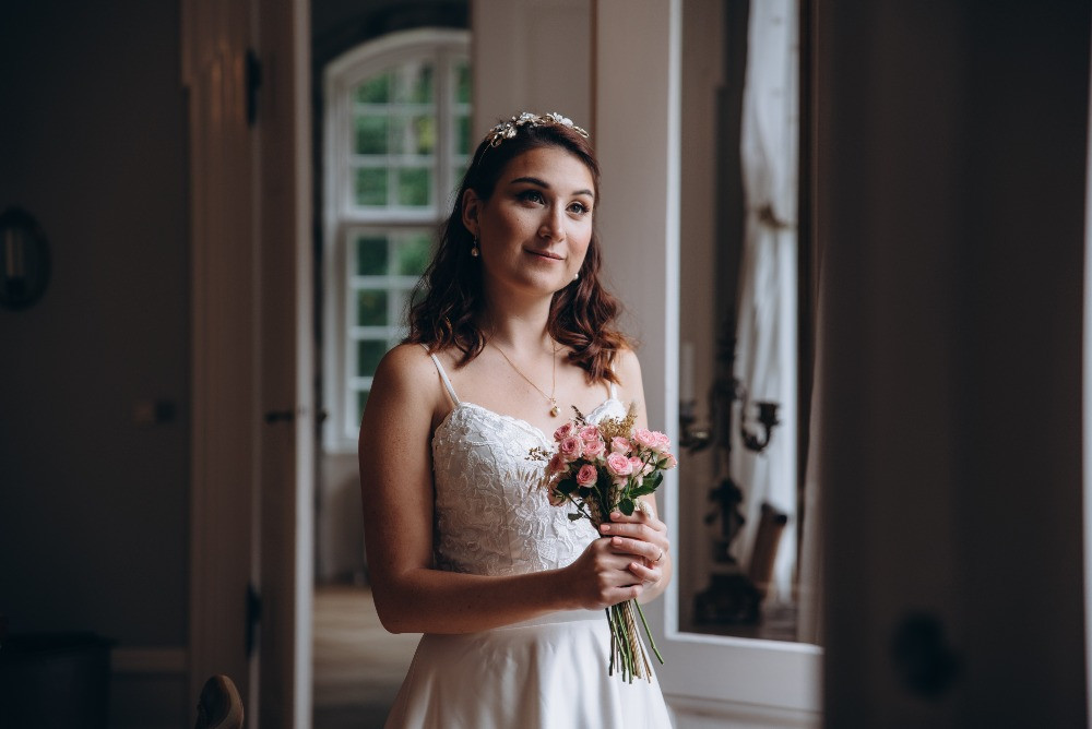 A bride posing to the photographer with Small winter wedding bouquet