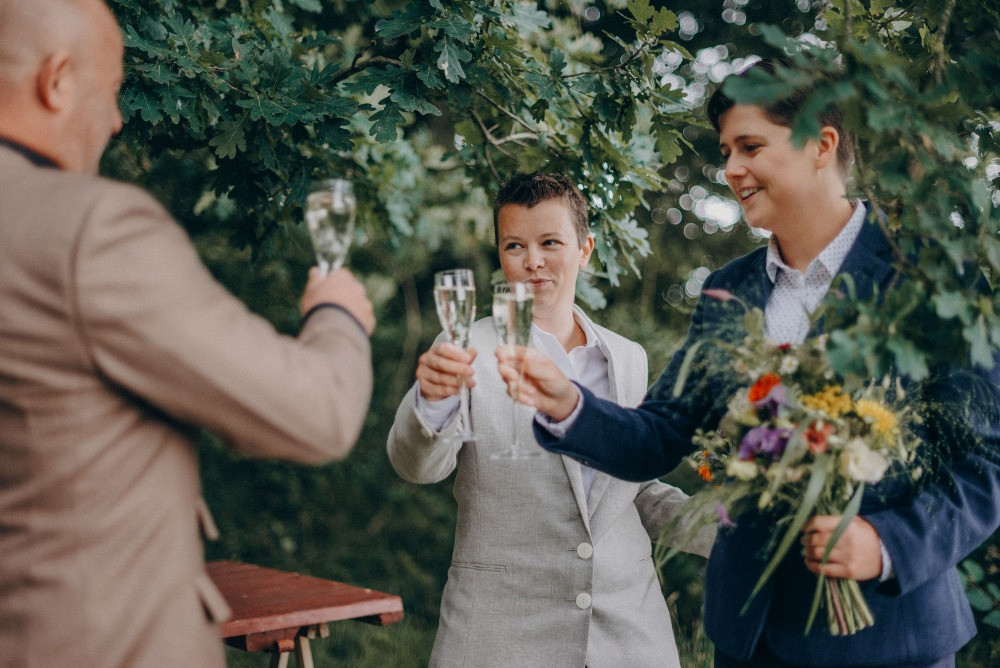 Lesbian couple toasting with the registrar after their wedding ceremony in Denmark in Lejre