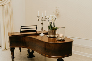 A romantic set up of a piano, one of the many details that go into preparing Danish weddings in Maribo.