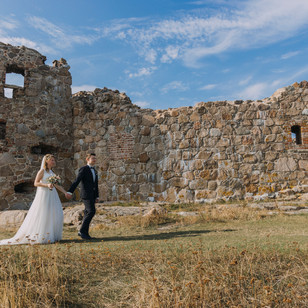 Newlyweds exploring Hammershus Ruins on Bornholm Island during their adventure wedding abroad.