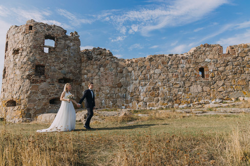 A couple holding hands and walking through the impressive Hammershus Ruins during their Denmark wedding at Bornholm Island, one of the best places to elope to for small weddings abroad.