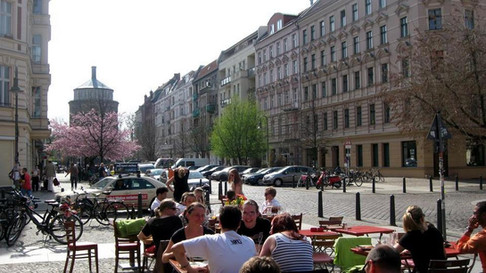 People sitting in cafe at one of cozy Copenhagen streets.