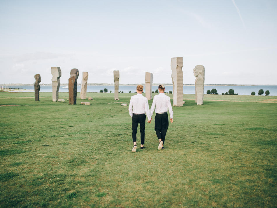 A same-sex marriage couple holding hands and eloping abroad to have their island wedding in Denmark at Dodecalith.