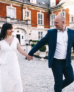 A couple holding hands and walking through the Hvedholm Castle courtyard, one of the coziest castles to get married in.