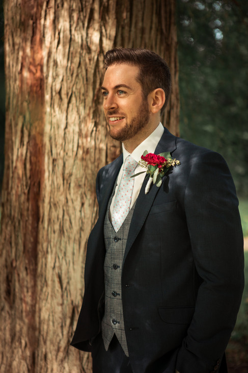 A groom posing by a tree in a Denmark park during his same-sex wedding adventure abroad.