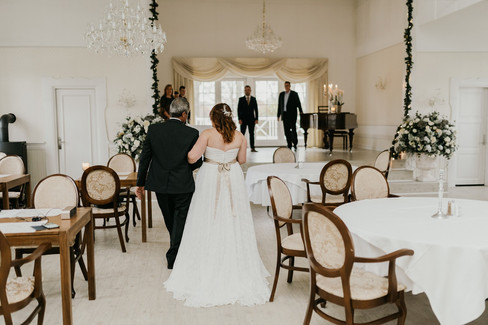 A bride walking down the aisle with her father in a hotel selected as our Denmark elopement packages at Lolland Island in Maribo town.