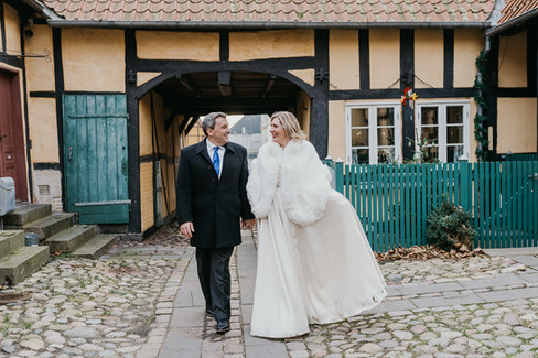 A husband and wife holding hands and smiling as they stroll through the streets in Maribo while getting married in Denmark