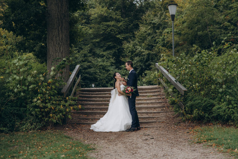 A romantic photograph of newlyweds in nature surrounded by trees during their elopement in Denmark on Lolland Island at Maribo.
