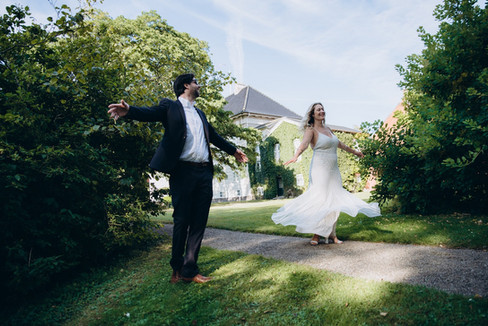 Newlyweds dancing with their arms open wide during their Nordic wedding at the Lolland-Falster islands as they enjoy getting married in Denmark.