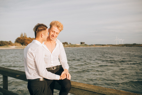 A gay couple sitting on the pier and smiling as they enjoy their LGBT wedding abroad in Denmark.