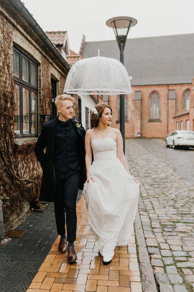 Husband and wife walking through the streets of Denmark during their winter wedding adventure on Mon Island as they enjoy their Danish wedding abroad.