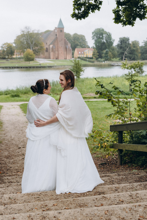 Newlyweds embracing during their LGBT wedding at Lolland Island by the Maribo Lake on Lolland Island, one of the most romantic Denmark wedding venues.