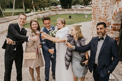 A group of friends toasting with newlyweds in front of the Old  Hojerup Church during a small intimate wedding abroad.