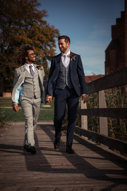 A couple walking by the Great Cathedral and holding hands during their elopement in Denmark, made possible by one of our wedding packages abroad for two, ideal for your gay marriage in Denmark.