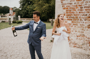 Newlyweds popping champagne at their dream Denmark wedding venue during their small wedding abroad adventure.