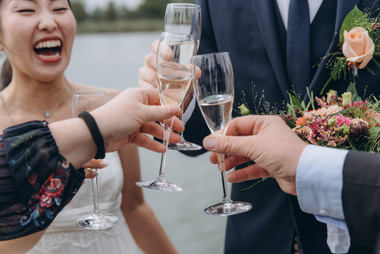 A close-up of champagne glasses toasting during an intimate wedding abroad, one of the many details that go into our wedding packages abroad for two.