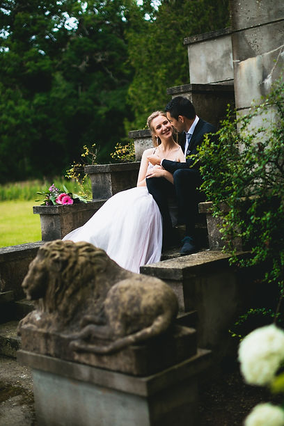 Newlyweds sitting on stone steps at a Nordic park during their romantic elopement abroad.