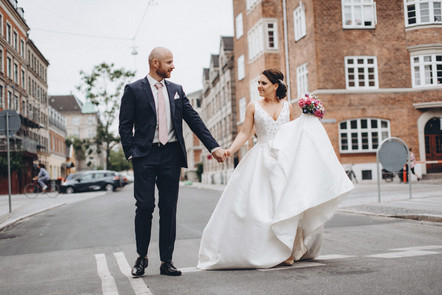 A couple holding hands after getting married in Copenhagen. Their Denmark city hall adventure made their civil wedding abroad in Denmark truly special.
