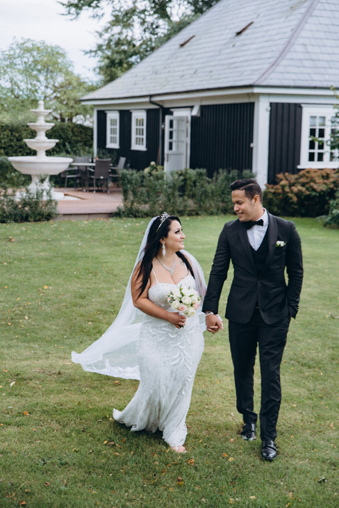 Newlyweds walking through the hotel outdoor area as they hold hands and talk about their adventure elopement in Lolland Island as Denmark is one of the best places to get married abroad.