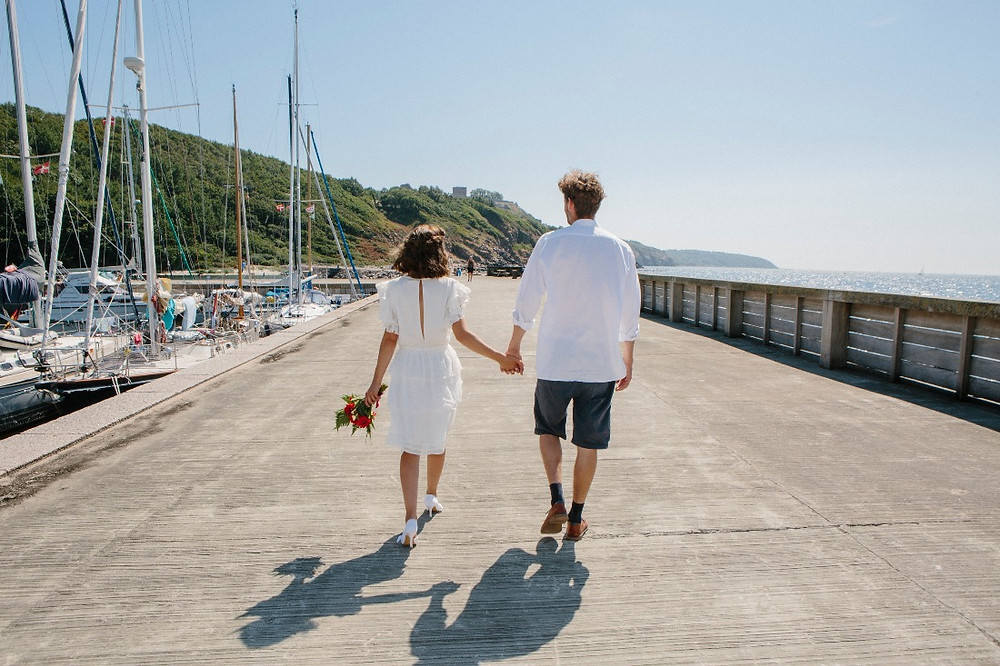 the newlyweds walk along the pier hand in hand, after they had all inclusive wedding abroad