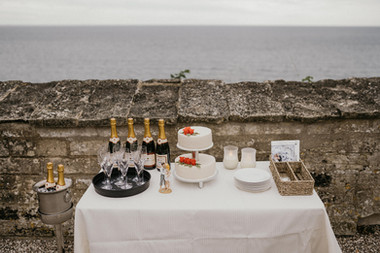 A romantic set up with a wedding cake and champagne by the Baltic Sea, one of the many details of what a romantic elopement in Denmark with Nordic Adventure Weddings will look like.