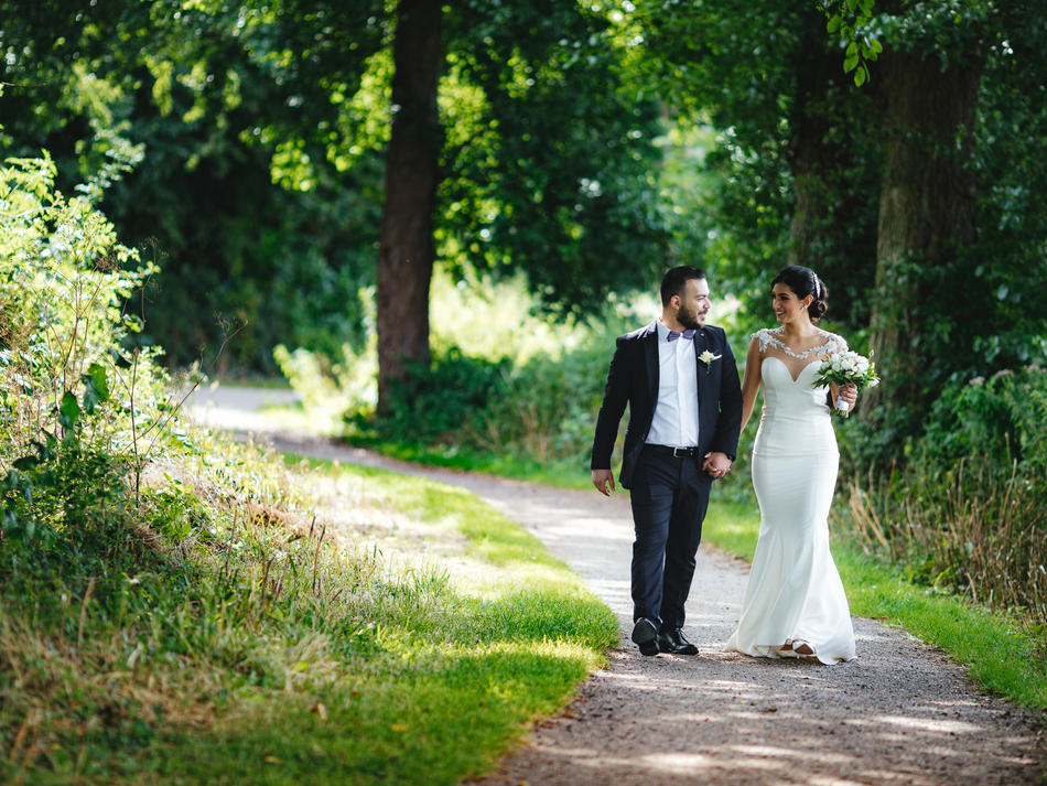 Holding hands and walking down the forest path, a couple is enjoying their elopement abroad to Denmark.
