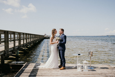 Husband and wife holding hands at the Hestehoved Jetty during their beach wedding in Lolland island, one of the best Denmark wedding venues