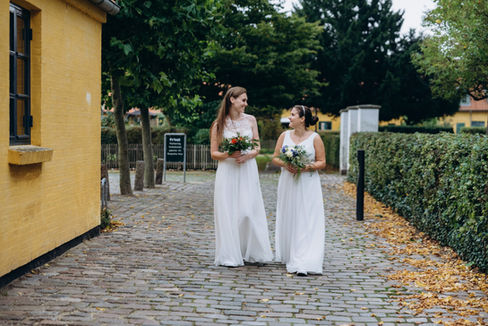 Two brides walking through the picturesque Maribo town as they smile on their same sex marriage in Denmark