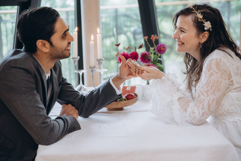 A couple getting ready to have their meal after their small wedding abroad.