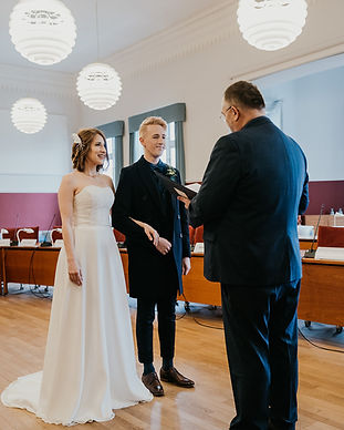 A couple smiling and holding hands during their Denmark city hall wedding made possible by Nordic Adventure Weddings