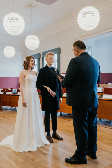 A romantic moment between husband and wife as they embrace hand during their town hall wedding in Denmark.