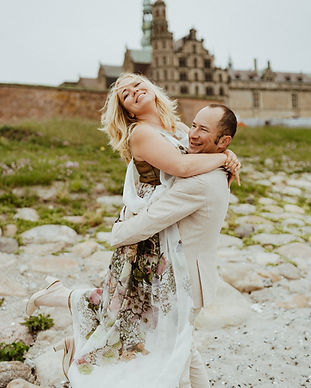A husband lifting up his bride as they renew wedding vows in Hamlet's Elsinore Castle in Denmark.