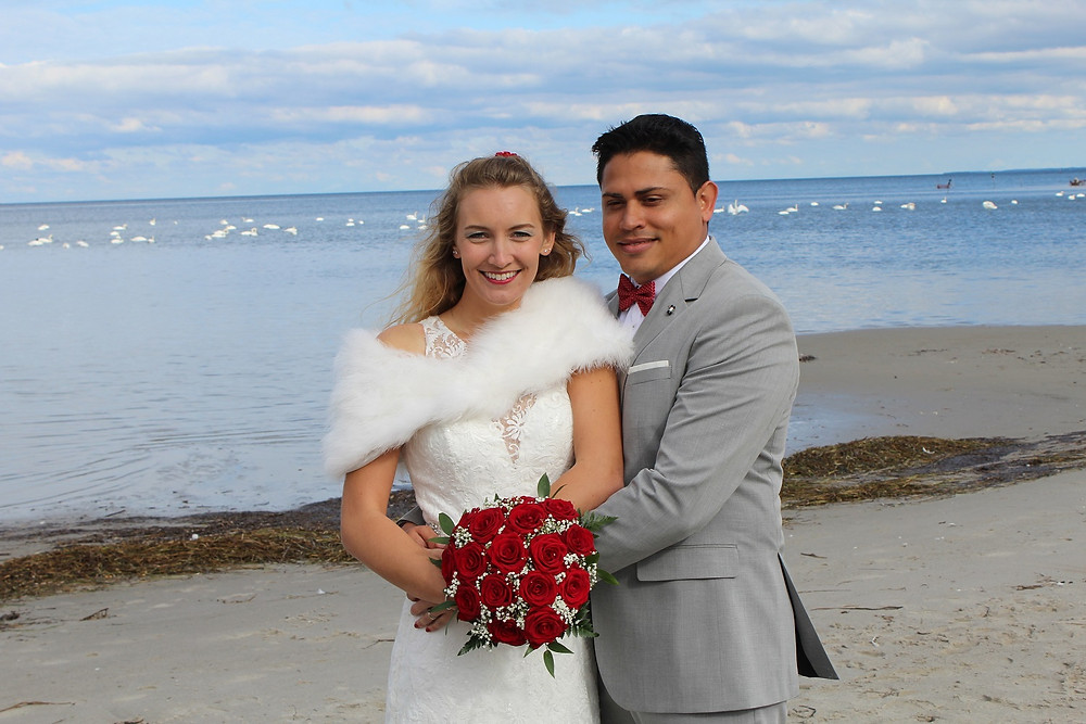 Newlyweds on the beach with red roses bridal flowers, right after their beach wedding in Denmark.