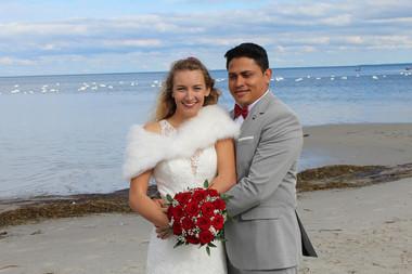 A groom embracing his bride as they enjoy their Scandinavian beach wedding in Denmark at Lolland Island.