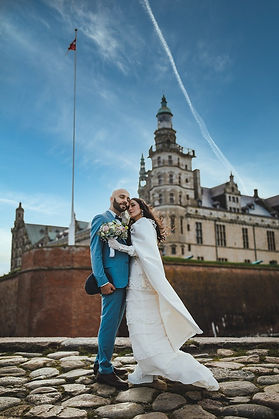 A couple posing in front of Kronborg Castle, which is Hamlet's Elsinore Castle, during their small castle wedding abroad.