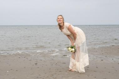 A bride posing and having fun during her dream beach wedding in Denmark.