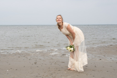 A bride posing and having fun during her dream beach wedding in Denmark.