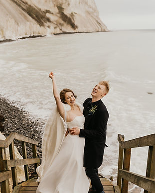 Newlyweds celebrating their small wedding abroad at Mons Klint as they have fun during their wedding island adventure.
