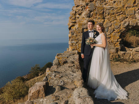 A couple standing on the castle ruins Hammershus, one of the best destination wedding locations for couples looking for a laid back elopement abroad.
