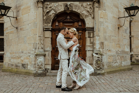 Husband and wife embracing each other as they renew vows abroad at Hamlet's Elsinore Castle in Denmark
