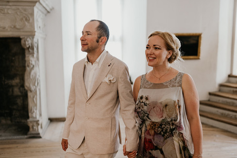 Husband and wife holding hands as they walk through Hamlet's castle during their adventure wedding in Denmark.