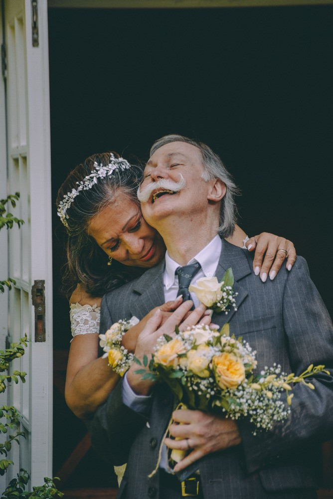 Senior bride holds her smiling groom while they get married in denmark