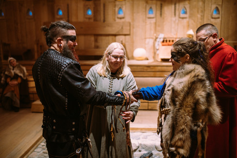 A man and wife performing the handfasting ceremony during their viking-themed wedding in Denmark.