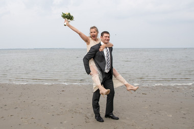 A groom giving his happy bride a piggyback ride while on getting married in Denmark.