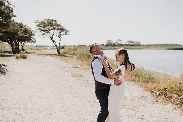 A couple embracing romantically, dancing and laughing during their outdoors wedding in Denmark's Hestehoved Jetty made possible by our adventure elopement packages.