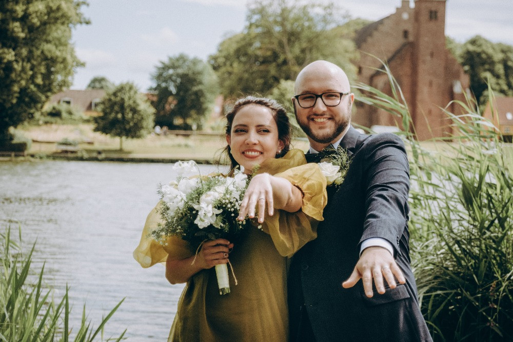 A couple showing their hands with rings after they get married in Denmark.