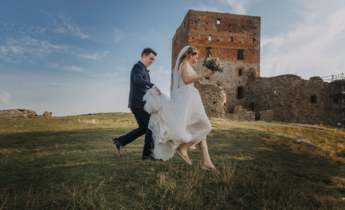Husband and wife leaping for joy in front of the Hammershus Ruins during their adventure elopement in Denmark at Bornholm Island.