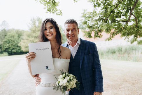 A couple holding their wedding paperwork after their wedding ceremony in Denmark.
