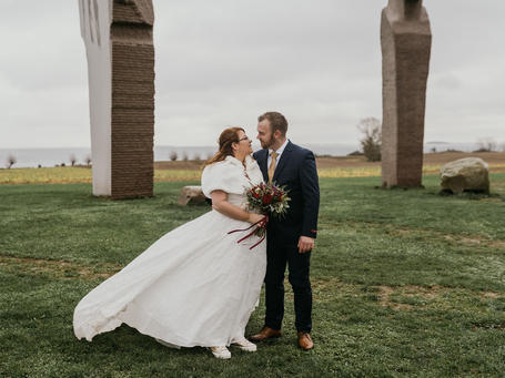 An international marriage couple embracing at Dodecalith, one of the best destination wedding locations in Denmark for art lovers.