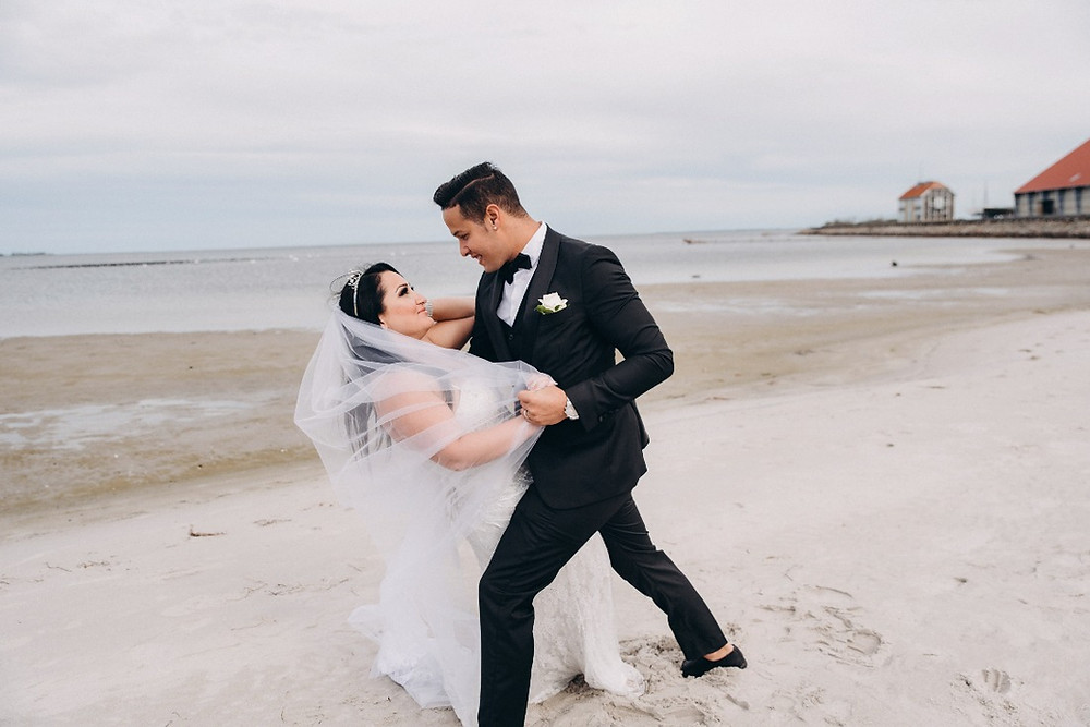 A couple dancing at the beach after they hold their small intimate beach wedding